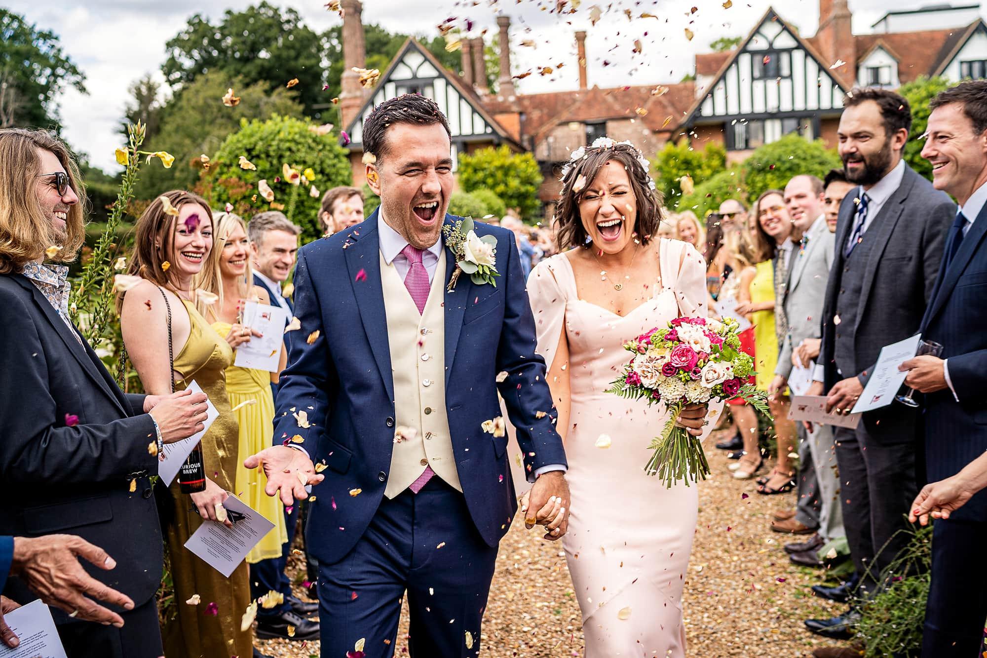 bride and groom walking through confetti at Brickwall house wedding venue Northiam Sussex