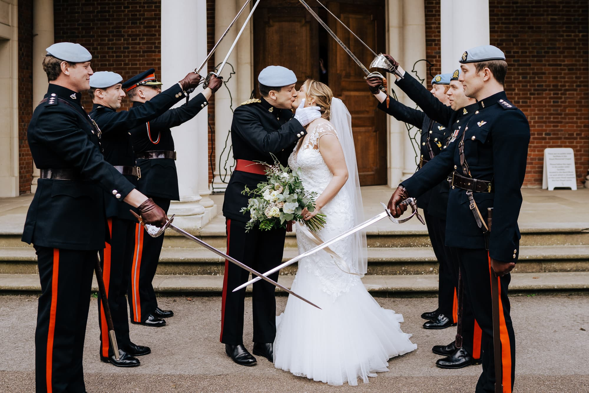 military bride and groom kiss under guard of honour