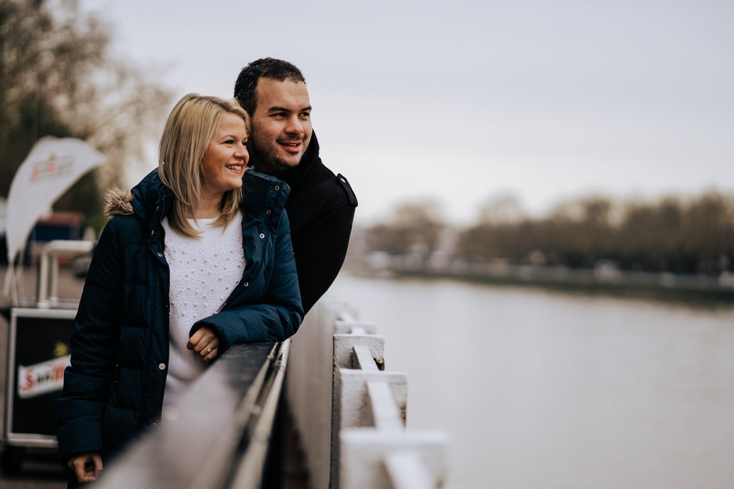 Loving pre wed couple pictured overlooking river taken during their pre wedding engagement shoot at Fulham FC