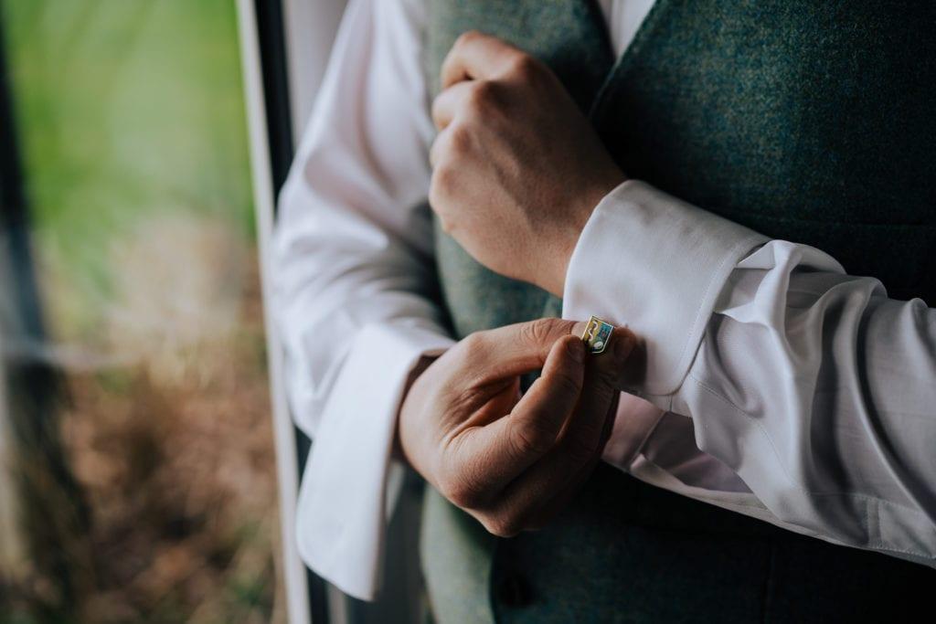 groom putting cufflinks on