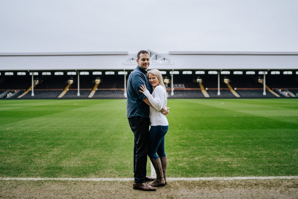 Tender moment captured of a fun couple during their pre wedding photo shoot at Fulham FC