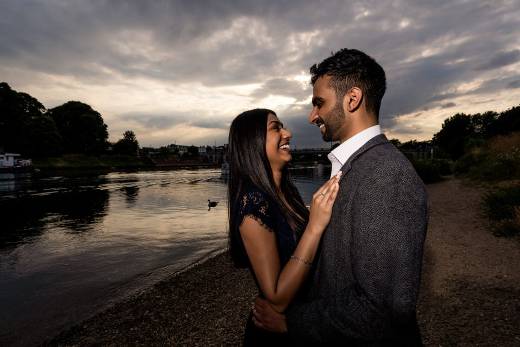 couple hugging next to the river Thames | Surrey Engagement Shoot