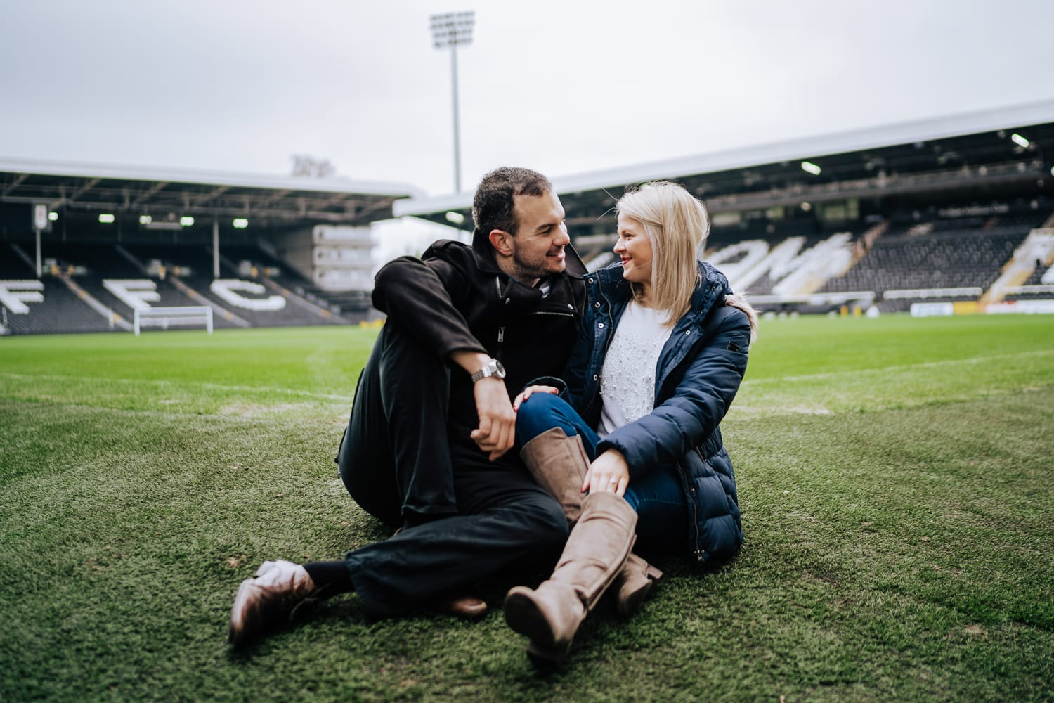 Cute photos of young couple sat on the pitch of Fulham FC during Engagement shoot