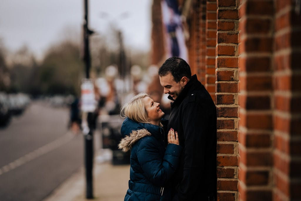 Young lovers stare into each others eyes during pre wedding shoot at Fulham FC