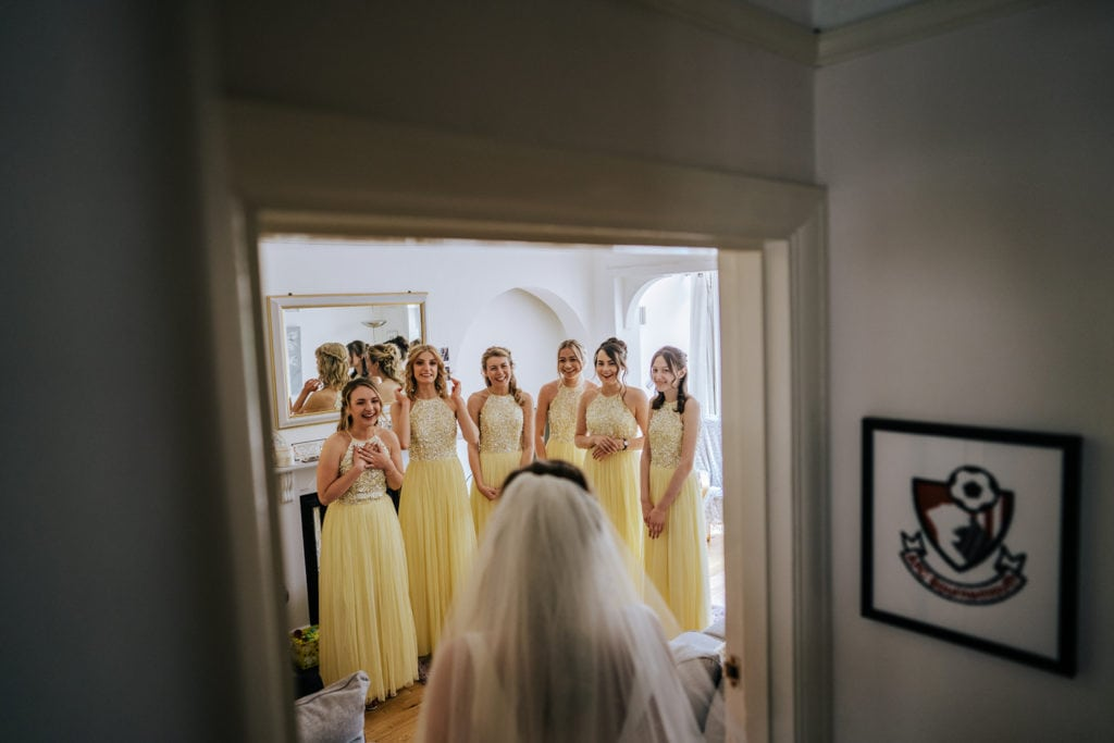 bridesmaids see bride in her dress for first time