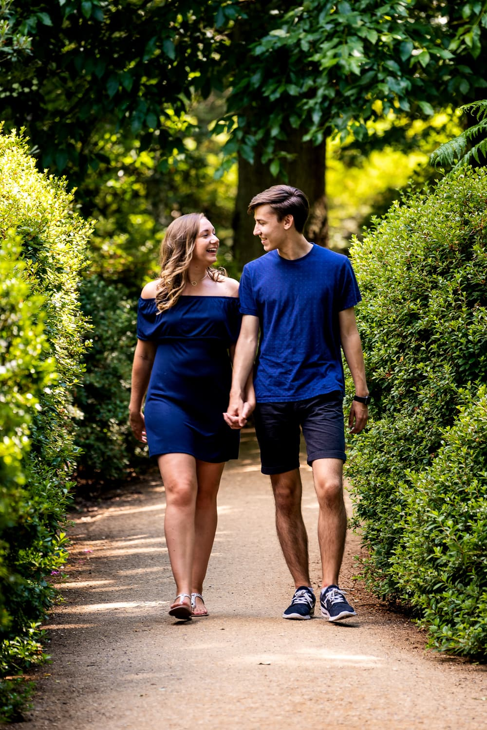 Couple walking through the beautiful surroundings of Richmond Park in Surrey smiling and chatting during their engagement photo shoot