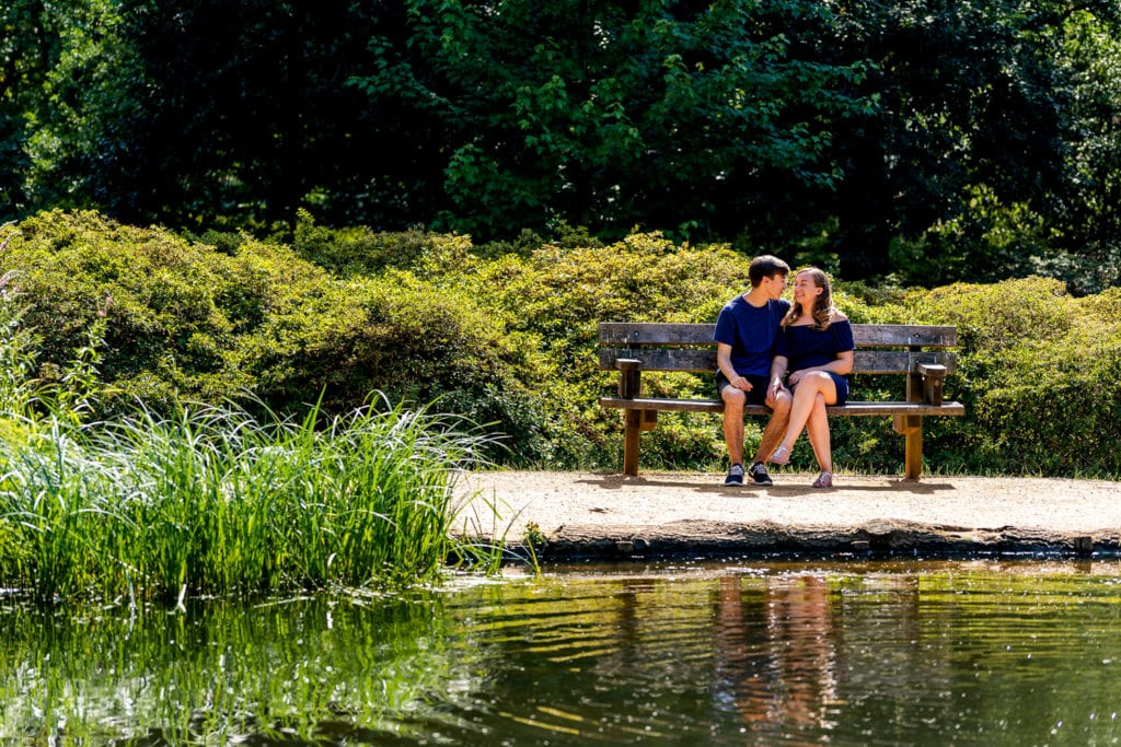 Long distance pre wedding engagement photo of young lovers sat on a bench at the stunning Richmond Park Surrey