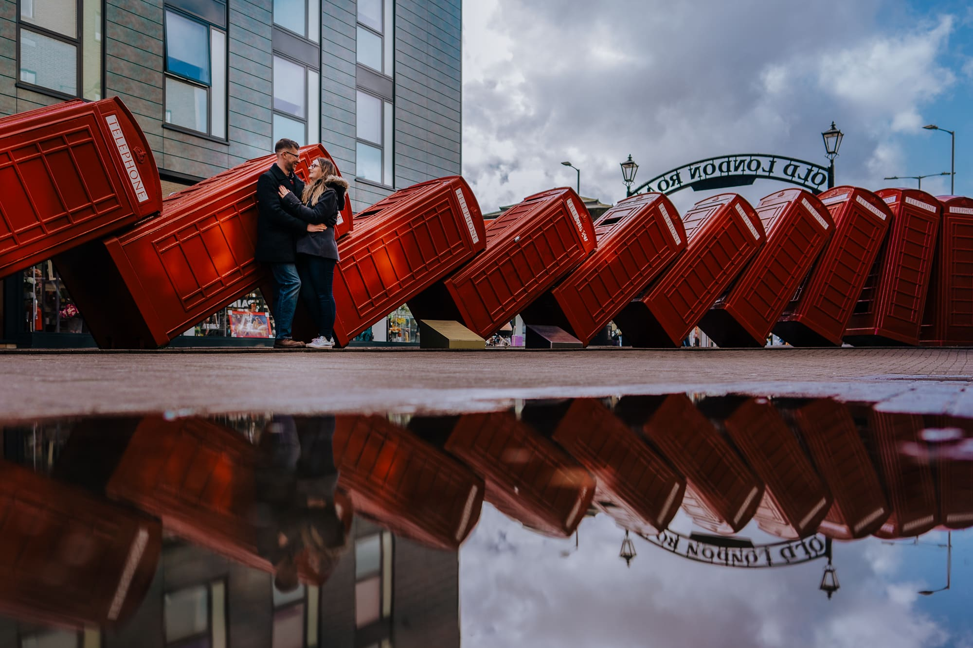 couple pose in front of out of order sculpture kingston upon thames