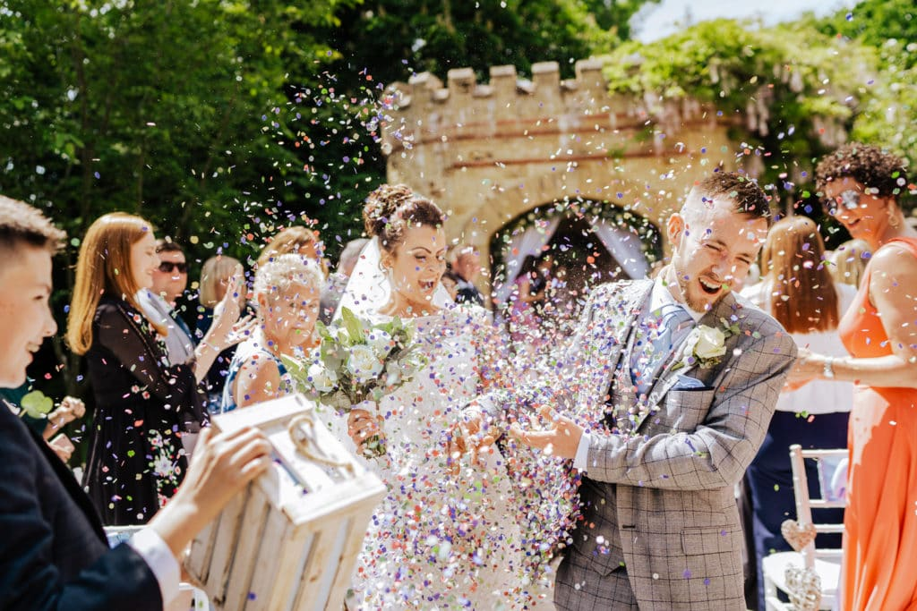 groom being hit in face with lots of confetti