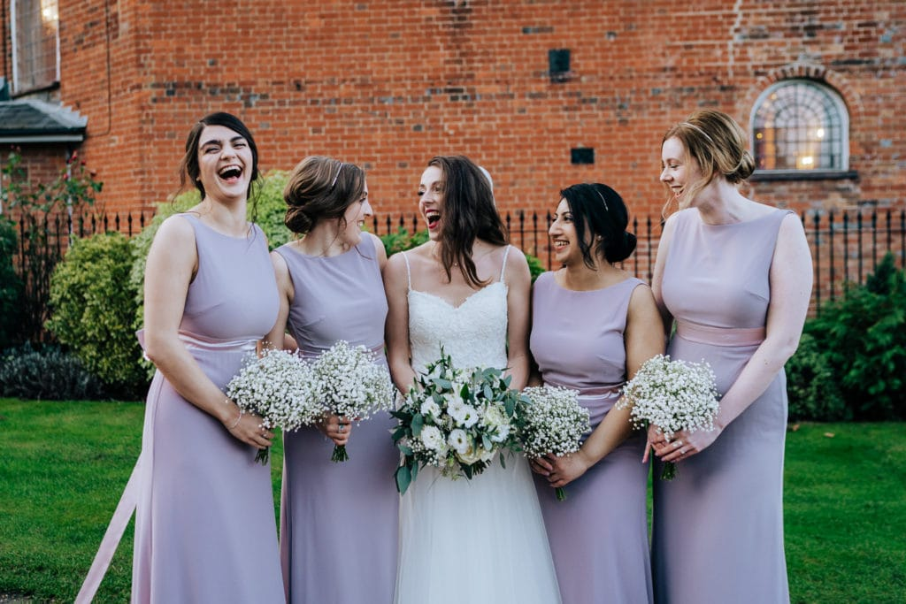 bride and bridesmaids laughing during group photos