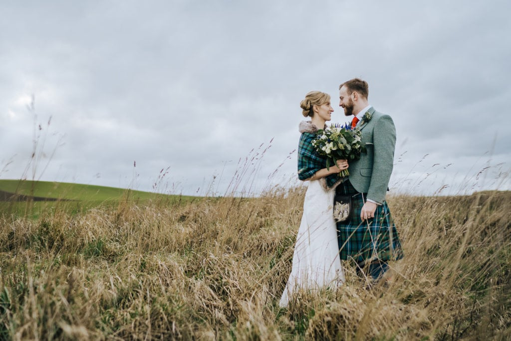 Newlyweds looking out to sea at Kinkell Byre wedding Venue