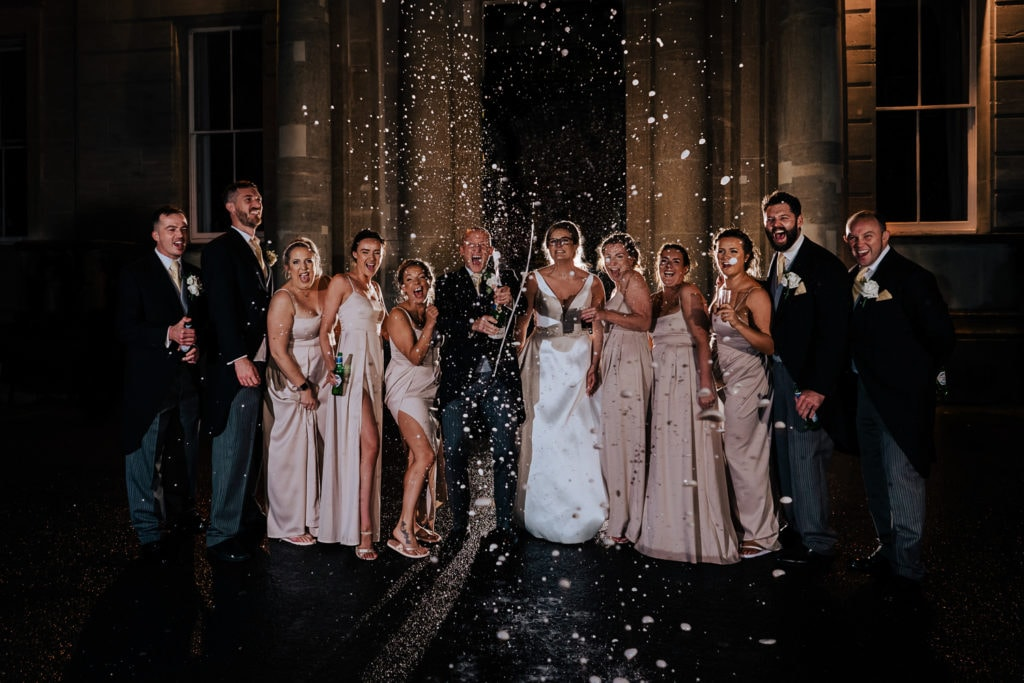 Bridal party spraying champagne during reception