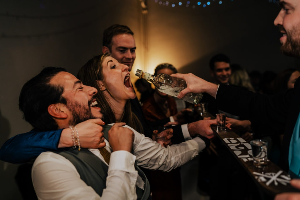 wedding guests drinking from ski bar