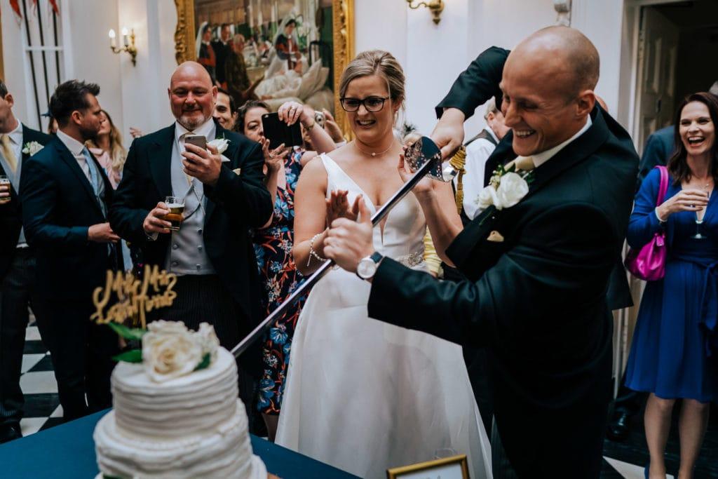bride and groom cut cake at RMAS Sandhurst