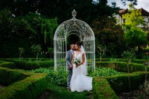 bride and groom pose in gardens of Ravenswood Wedding Venue