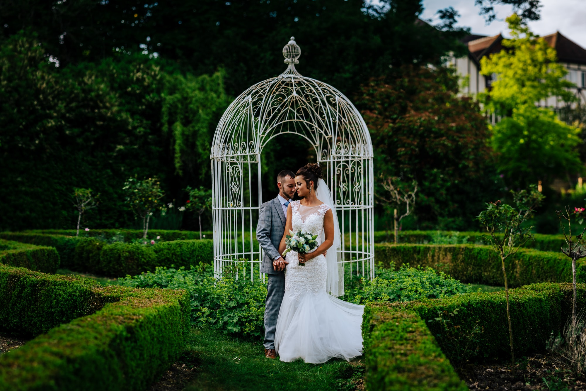 bride and groom pose in gardens of Ravenswood Wedding Venue