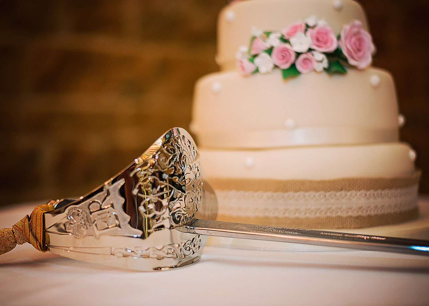 military sword resting next to wedding cake
