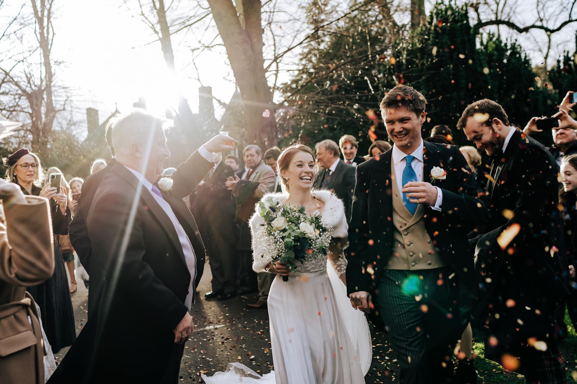 Bride and groom walk through confetti tunnel at Hampton Court Winter wedding