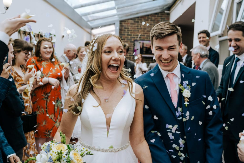 creative wiltshire wedding photographer capturing a bride and groom waling through confetti tunnel