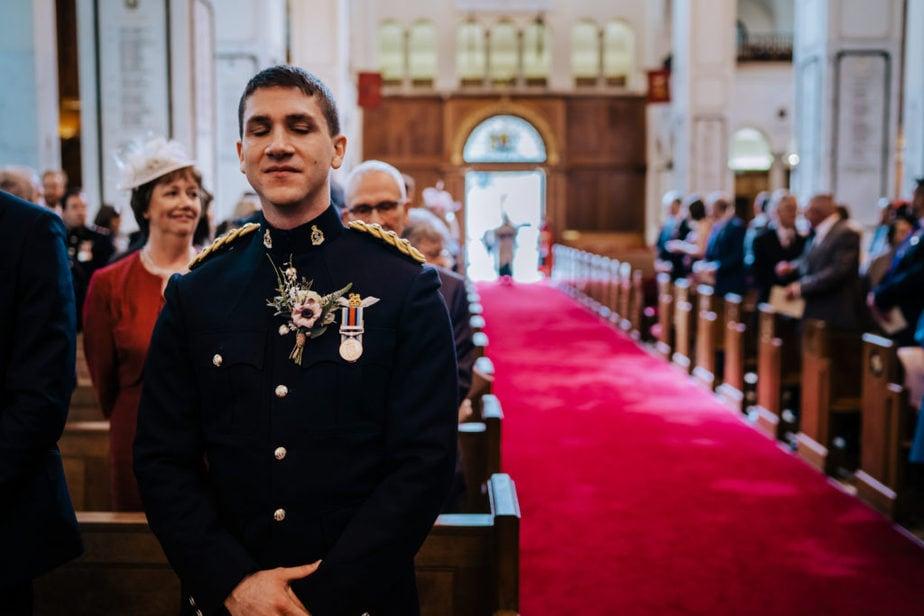 nervous groom awaiting bride at UK military wedding