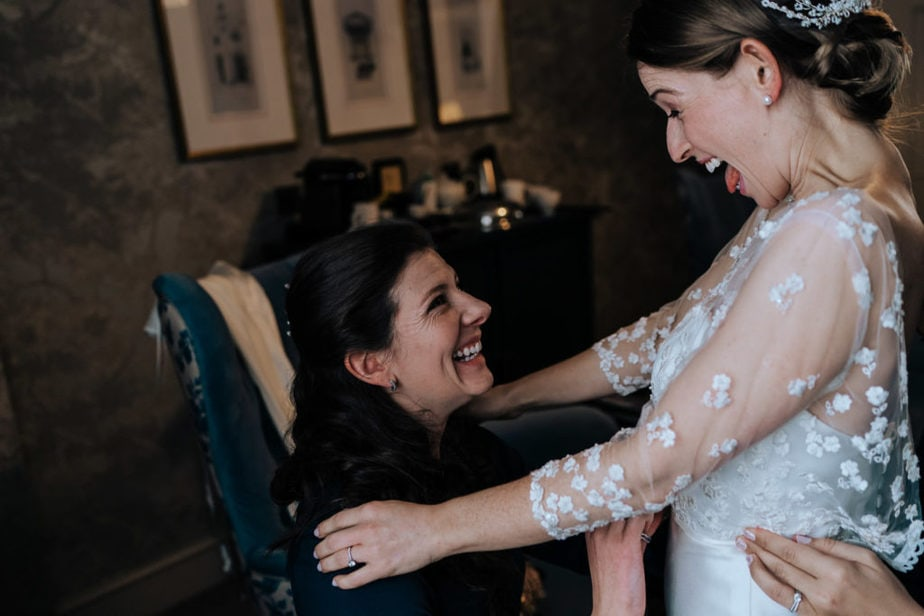 bride has fun with her bridesmaids getting ready at a fantastic surrey wedding