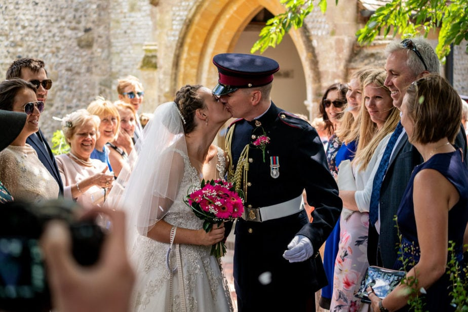 Bride and groom kiss after ceremony captured by military wedding photographer