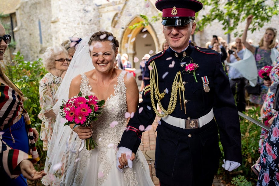 military groom and bride walking through confetti