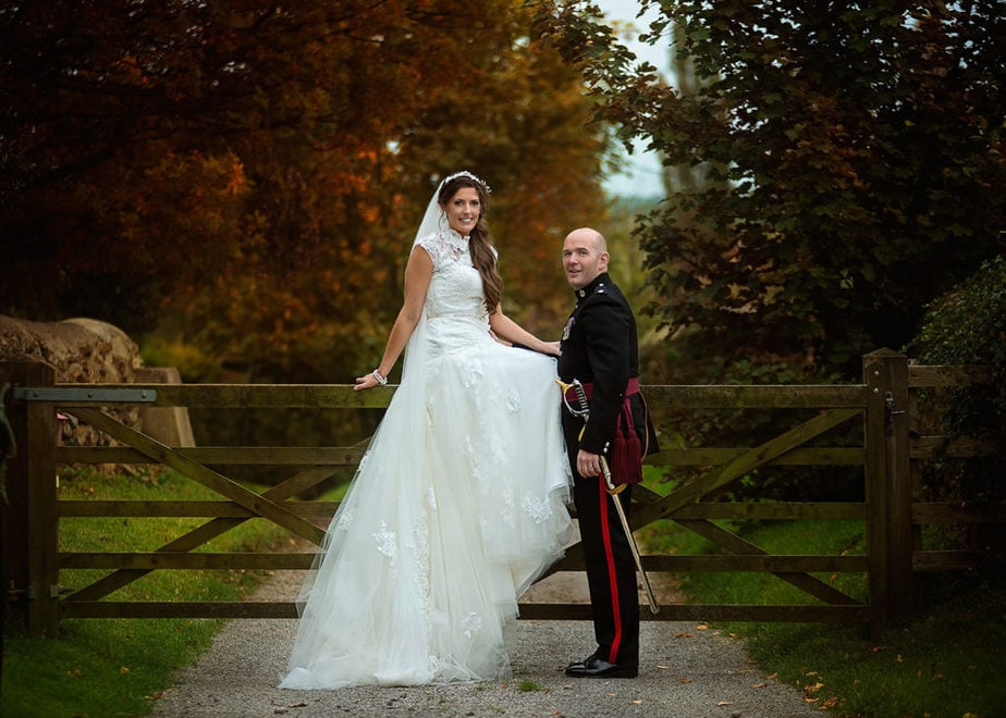 couple posing duiring autumn military wedding