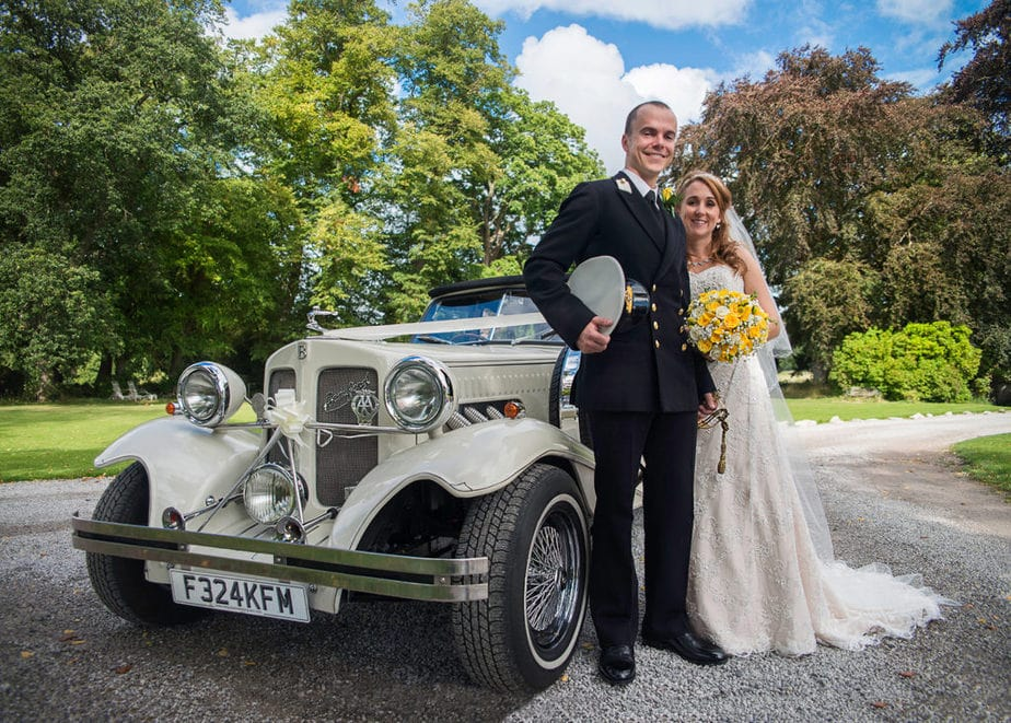 navy groom and bride posing with wedding car at UK military wedding