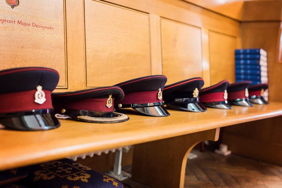 military groomsmen hats resting on church pew