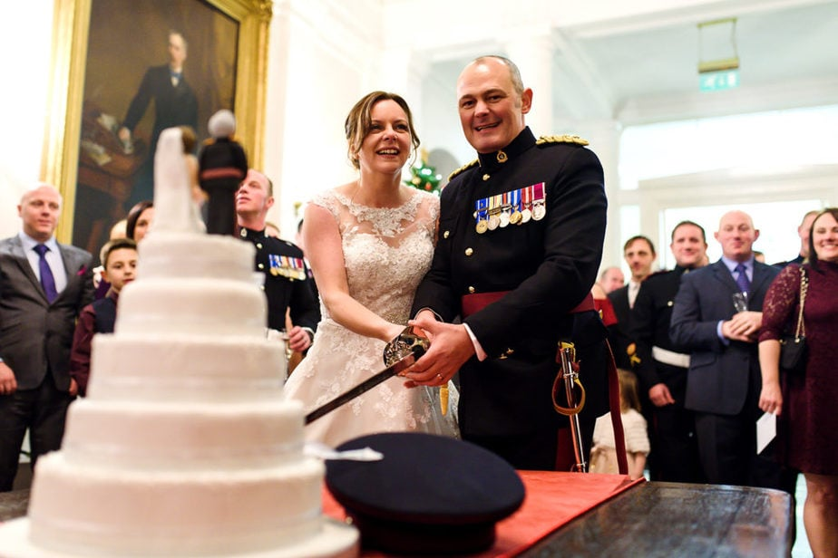 military bride and groom cutting cake