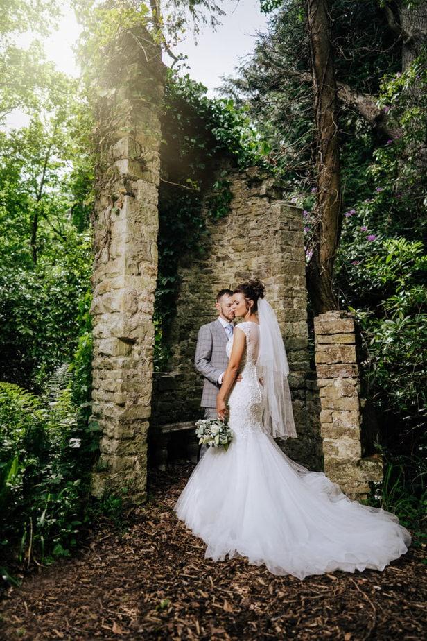 bride and groom portrait next to ruins at stunning Surrey wedding