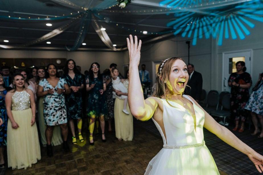 bride throws a bouquet durin
