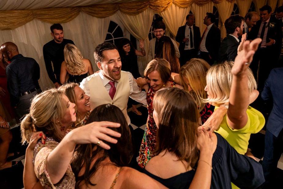 groom and guuests dance during fun Surrey summer wedding