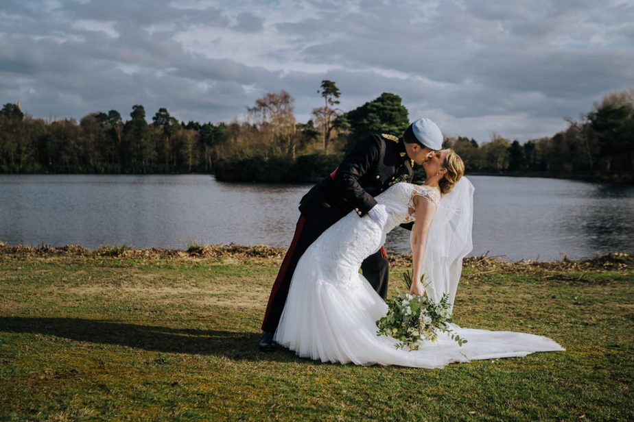 groom dips bride for romantic kiss during military wedding